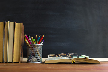 Glasses teacher books and a stand with pencils on the table, on the background of a blackboard with...