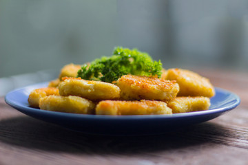 chicken nuggets fried to Golden brown with parsley on wooden background