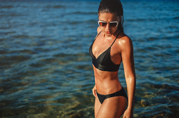 Wet girl with sunglasses standing in the sea water