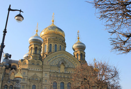 Church of the Assumption of the Blessed Virgin Mary in Saint Petersburg, Russia. Russian Orthodox Church Building with Ornamental Mosaic Facade and Golden Domes, Religious City Landmark.