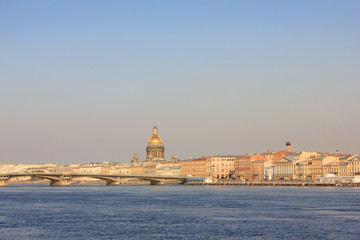 St. Petersburg Sunset Skyline View Over the River in Russia.Historical Russian Architecture with Classic Famous City Drawbridge and St. Isaac's Cathedral on Background with Empty Sky Copy Space.