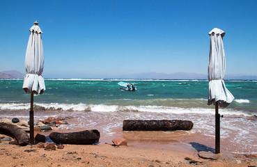 Closed sunchades at beach. Seascape Red Sea, Dahab, Sinai, Egypt.