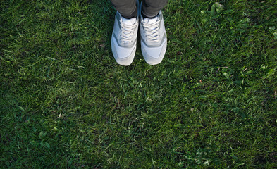 Sports shoes sneakers on fresh green grass. Top view.