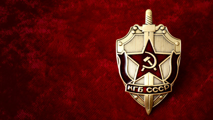 Secret service, intelligence agency, and espionage concept with cold war era KGB badge from the former USSR, on red background with copy space