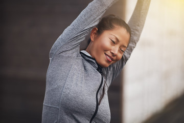 Young Asian woman in sportswear stretching outside before exerci