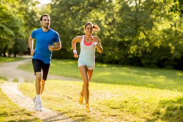 Wall Murals Jogging Young couple running in the park on a sunny day