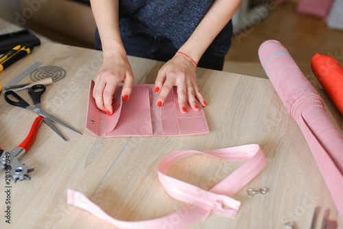 Craftswoman With Manicure Making Pink Leather Handmade Purse At Home