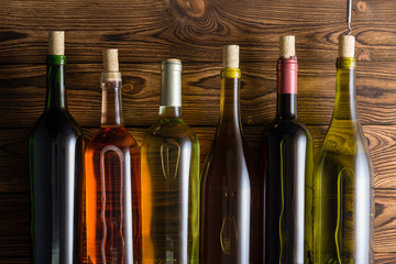 Six bottles with wine against wooden background