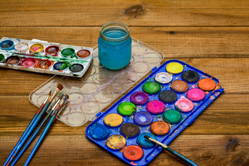 Set of watercolor paints, art brushes, glass of water on old wooden table.