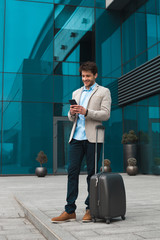 Reaching the goal! Full length portrait of the young smart elegant businessman checking e-mail on mobile phone, while standing near his luggage outdoors.