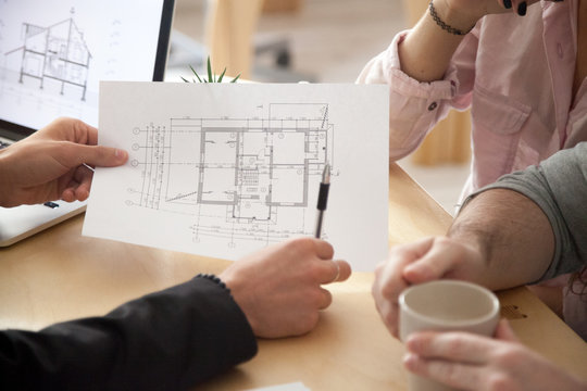 Architect or interior designer showing new apartment plan to couple at meeting, realtor consulting customers making real estate offer, mortgage loan investment and construction concept, close up view