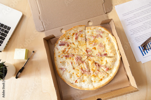 Italian pizza with ham and cheese in cardboard box on work