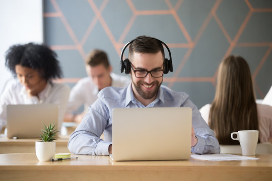 Smiling businessman wearing headphones watching video or consulting client online looking on laptop in office, happy millennial employee in headset making videocall using computer app in coworking