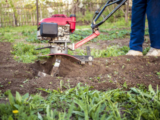 close up rotating cultivating tiller in the garden