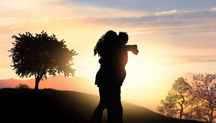 young couple hugs each other on the hill at sunset