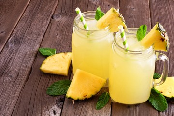 Pineapple juice in mason jar glasses on a rustic wood background