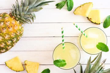 Two glasses of pineapple juice with fruit. Top view frame on a white wood background.