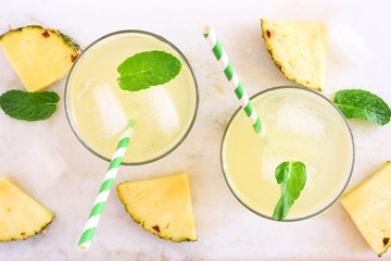 Two glasses of pineapple juice with mint. Top view on a white marble background.