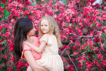 Adorable little girl with young mother in blooming cherry garden on spring day