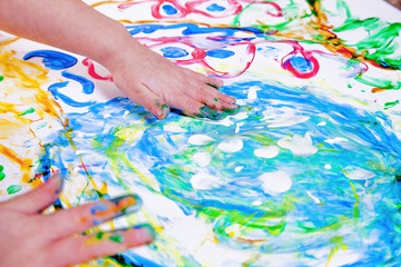 Child girl painting with colorful hands.