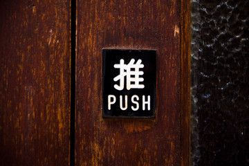 Sign push in chinese hieroglyph on wooden door close up in Hong Kong