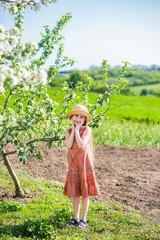 little girl is stroking a calf in a field.