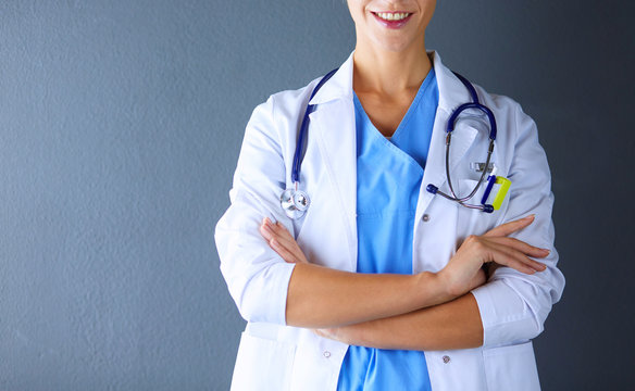 Portrait of young woman doctor with white coat standing in hospital.