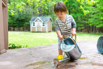 Toddler boy playing with a watering can outside