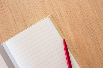 Office desk- blank notebook page and red pen on wood office table background.