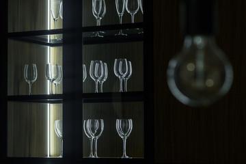 Empty clean glasses organized in wooden cupboard
