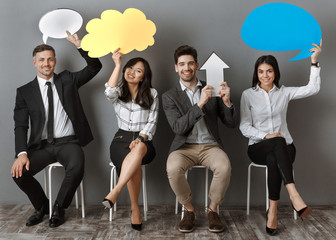 smiling multiethnic business people with paper chat bubbles and arrow waiting for job interview
