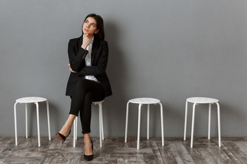 pensive businesswoman in suit waiting for job interview