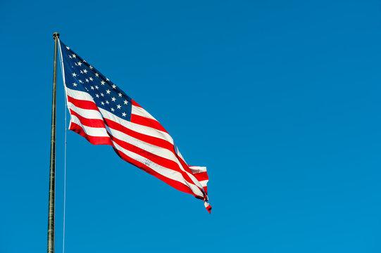 Floating american flag against blue sky, New-York city, USA