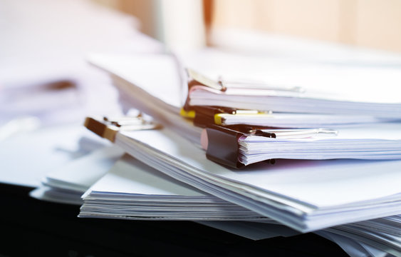 Stack of papers documents in archives files with clip papers on table at offices,  Busy offices and Pile of data unfinished folders on office desk indoor near window,  Business concept.