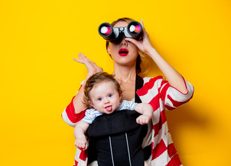 little baby in carrier and mother with binoculars on yellow background