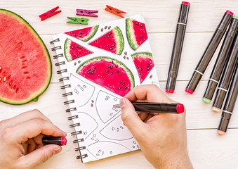 man hands drawing a watermelon sketch on wooden background with markers