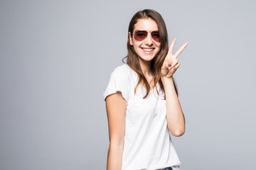 Playful young woman gesturing peace sing and smiling while standing against white background