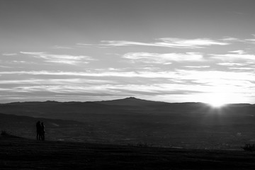 A couple looking at sunset from the top of Subasio mountain (Umbria, Italy)
