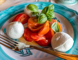 Buffalo mozzarella with fresh tomatoes and basilic at Positano  restaurant. Selective focus.