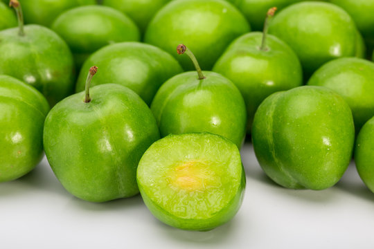 Close Up Of Green Plums Or Greengage showing the flesh and the seed of the fruit Isolated On White Background, Popular Spring Fruits With A Very Sharp Sour Taste Originated In Iran