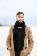 European good looking male person with beard wearing coat and scarf standing in white snow background. Concept of fashion and seasonal winter inspiration.
