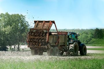 tracteur agricole avec remorque épandage de fumier en action sur le champ