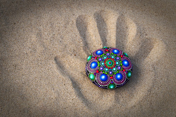 hand painted mandala rock on sand