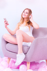 Girl in white underwear and white sneakers listening to music with headphones, holding smartphone while sitting on a purple armchair in the room with pink balloons on the floor