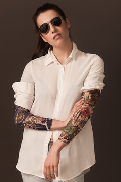 Beautiful and tough woman portrait wearing blouse and tattoo sleeves