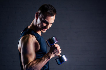 young man strengthens the muscles of the hands of dumbbells in the gym