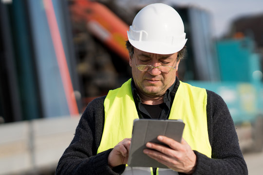 Engineer with safety vest and helmet looking at the construction site typing on a digital tablet computer