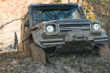 SUV is pulled out from puddle of mud by car winch.