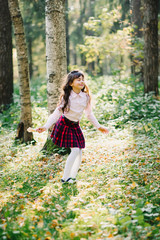 happy beautiful brunette girl is spinning and enjoying herself in the Park in autumn