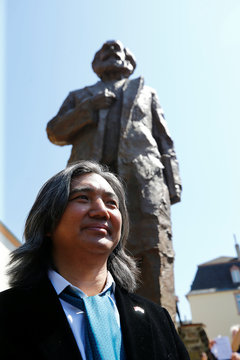 Chinese artist Wu Weishan poses next to his 4.4 metres (14 feet) high bronze statue of Karl Marx, donated by China, to mark the 200th birth anniversary of the German philosopher in his hometown Trier